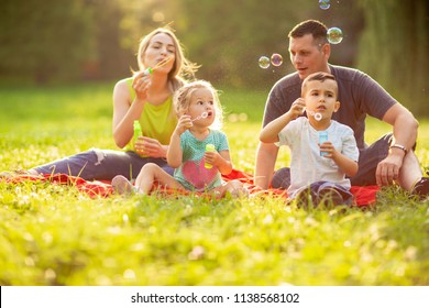 Young family with children blow soap bubbles outdoor
