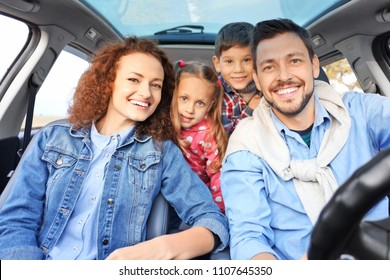 Young family with children in car
