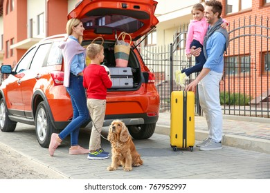 Young family with children and dog near car