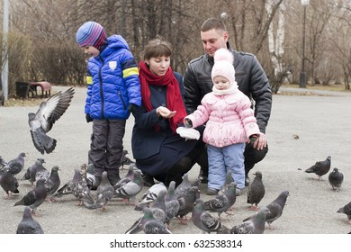 Young family with children feed pigeons in the park