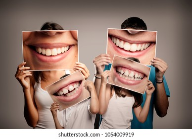 young family with children holding a picture of a mouth smiling on a gray background - Shutterstock ID 1054009919