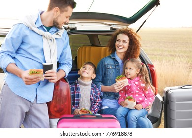 Young family with children near car, outdoors