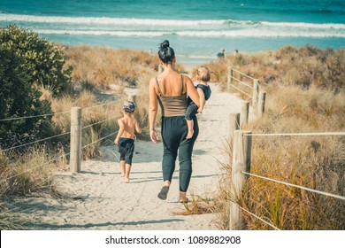 Young family with children playing on beautiful sunny sandy beach in New Zealand .