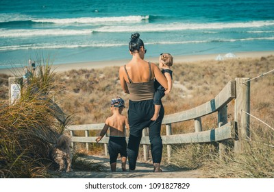 Young family with children playing on beautiful sunny sandy beach.