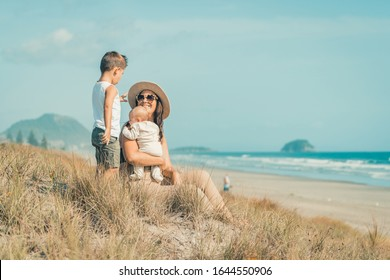 Young family with children playing on beautiful sunny sandy beach in New Zealand