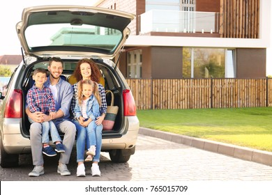 Young family with children sitting in car trunk near house