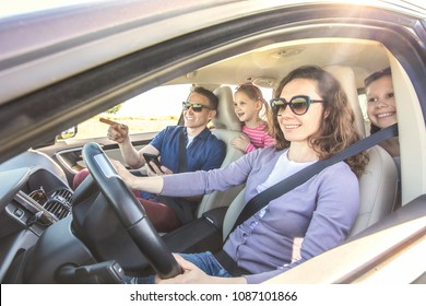 young family with children is traveling in a car on a journey. View inside the machine
