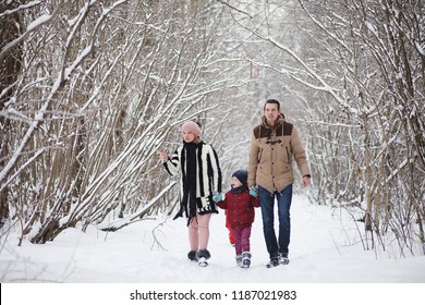 Young family with children are walking in the winter park. Winter walk of parents with children. Walking on holiday weekend in the winter.