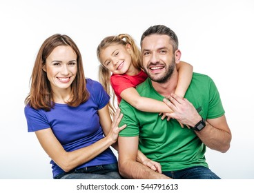 Young family in colorful t-shirts hugging and looking at camera isolated on white