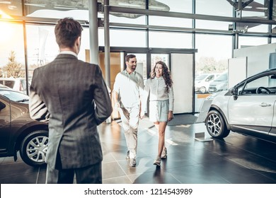 young family comes into Car dealership to choose the car to buy it. manager meets a young couple in car dealership