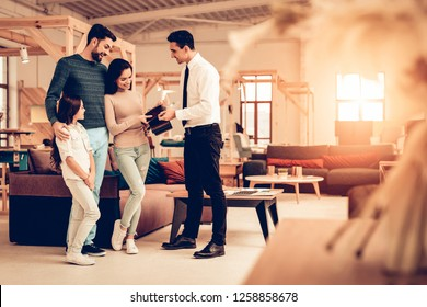Young Family Consulting With Furniture Seller. Happy Together. Bright Office. Sunny Day.Manager In Shirt And Tie. Business Meeting. Room Interior. Parents And Daughter. Look Around The Store.