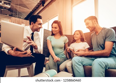 Young Family Consulting With A Furniture Seller. Happy Together. Bright Office. Sunny Day. Presentation On A Laptop. Make A Decision. Room Interior. Parents And Daughter. Sitting On Couch.