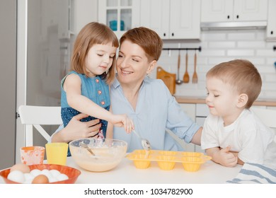 Young family cooking in the kitchen. Happy children with mom, smile, fill the cupcake molds with a batter. Concept preparation for Easter