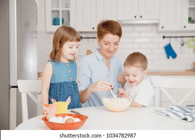 Young family cooking in kitchen. Happy children with mother smiling, laughing, mixing dough in bowl.