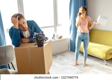 Young family couple bought or rented their first small apartment. Tired bored man looks exhausted. Young woman stand and talk on phone. Moving in and unpacking.