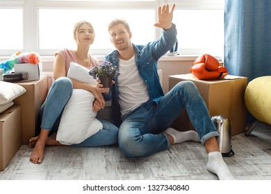 Young family couple bought or rented their first small apartment. They sit on floor among boxes with stuff. Guy point up forward. Dreaming together. Young woman hold pillow.