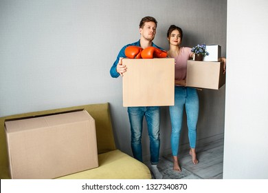 Young family couple bought or rented their first small apartment. They stand in room and hold boxes with stuff. Boxing gloves and flowers on top. Serious.