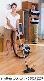 Young family couple doing regular clean-up at home and smiling