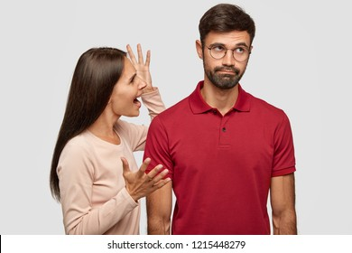 Young family couple have conflict. Angry brunette young European woman gestures with hands, shouts at husband who is guilty, stands together against white background, have dispute and quarrel