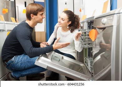 Young family couple looking at dishwashers in domestic appliances store