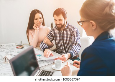 Young family couple purchase rent property real estate . Agent giving consultation to man and woman. Signing contract for buying house or flat or apartments. Discussion of size.