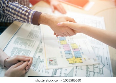 Young family couple purchase rent property real estate . Agent giving consultation to man and woman. Signing contract for buying house or flat or apartments. shaking hands . shaking hands Closeup
