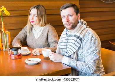Young family couple with serious faces quarrelling in cafe