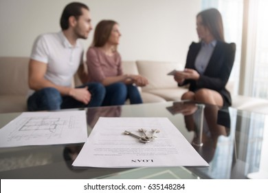 Young family couple sitting on sofa discussing first mortgage with agent, focus on loan agreement and keys, taking bank credit with easy terms of payment and low interest rate for purchasing property
