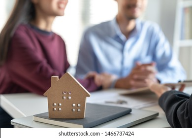 Young family couple talking with property real estate agent about home loan contract purchase agreement
