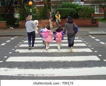 Young family crossing the famous abbey road crossing in londons west end.  Beatles done it years ago . but same crossing.