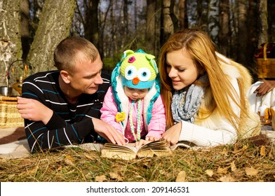 Young family with a daughter in autumn on the nature going