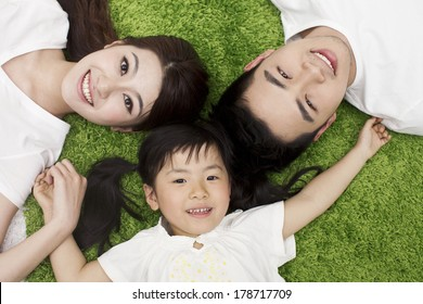 Young family with daughter lying on the grass
