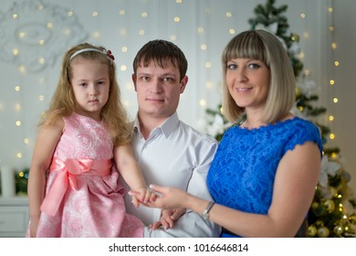Young family with daughter on the background of a Christmas tree with a blurry background
