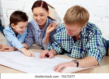 Young family discussing plan of new apartment