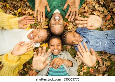 Young family doing a head circles and raising their hands on an autumns day