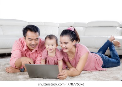 Young family enjoying leisure time while using a laptop and lying on the carpet