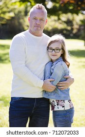 young family, father and daughter wearing casual outfits, outdoors in the park