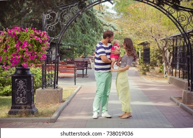 Young family of father mother and baby child daughter walking and holding each other on summer city street park close to bouquet of flowers and wooden bench.