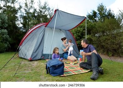 Young family, father and mother with two children camping in a tent outdoors.