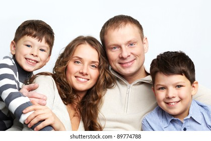 A young family of father, mother and two kids looking at camera and smiling