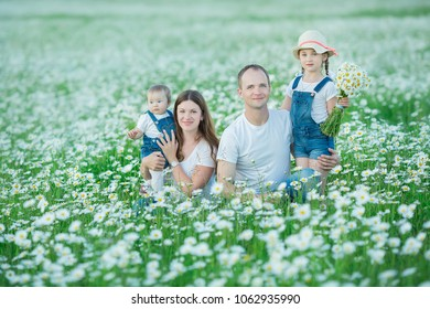 Young family in a field of flowers daises chamomile anjoy spa life happy together with cute faces in a village rustic motion.