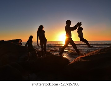 A young family of four enjoying a sunset walk along the cliffs at a San Diego beach. The father is lifting his young son across the boulders.