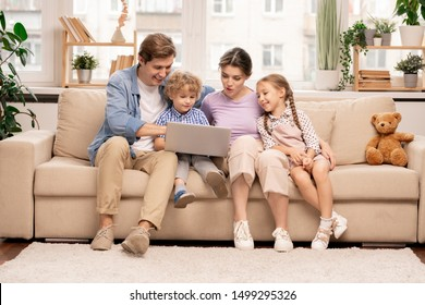 Young family of four with laptop surfing in the net while choosing movie or cartoons to watch at leisure