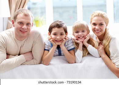 A young family of four looking at camera and smiling