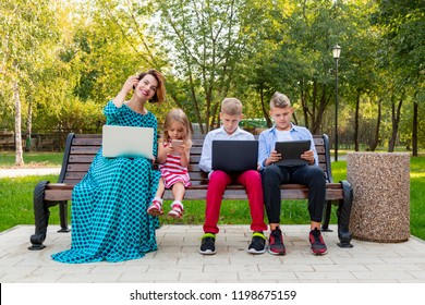 Young family with gadgets sitting on the bench