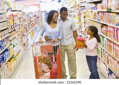 Young family grocery shopping in supermarket
