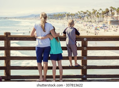 Young family hanging out on an ocean pier on vacation in Southern California