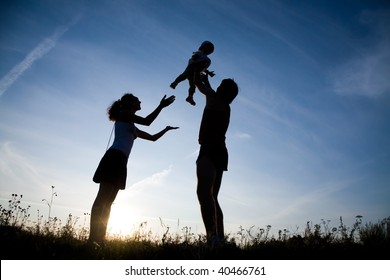 Young family happy play on the coast of background sunrise