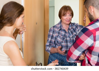 Young family having conflict with a elderly female neighbor at the door