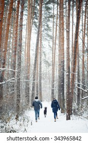 Young Family Having Fun with a Dog in Winter Forest on Vacations. Copy Space for Text. Selective Focus. Selective Focus.